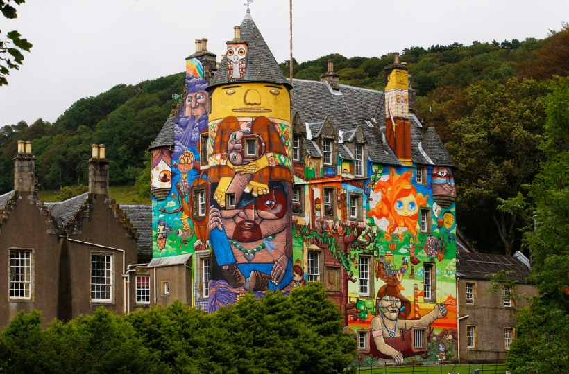 The Earl of Glasgow, Patrick Boyle (CENTRE L), and his son David, the Viscount Kelburn, pose for photographers as they look at graffiti paintings by Brazilian artists on the walls of Kelburn Castle near Largs, Scotland August 30, 2011. Boyle, the owner of the castle, has written to Historic Scotland asking if the mural, which was completed by Brazillian graffiti artists in 2007, can be kept after the three-year time limit, which was put on the artwork by the local council, has expired.        REUTERS/David Moir (BRITAIN - Tags: ENTERTAINMENT SOCIETY)